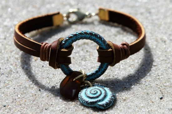 Verdi gris copper ring bracelet with amber seaglass and nautilus charms, knotted leather straps, lobster clasp 7.75""