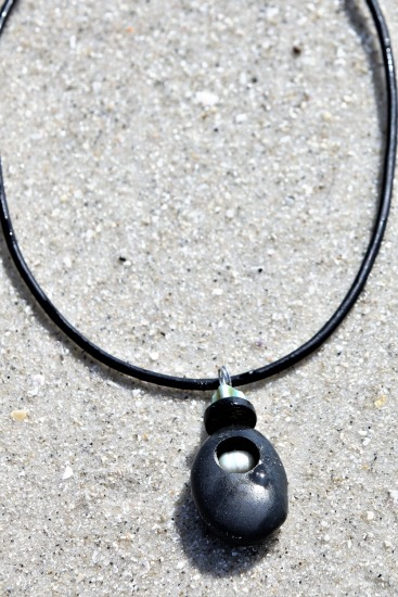 Rustic dark charcoal routed Beach Stone, inlaid with white barrel pearl, capped with ebony and sterling bead on black 3mm round leather cord 19""